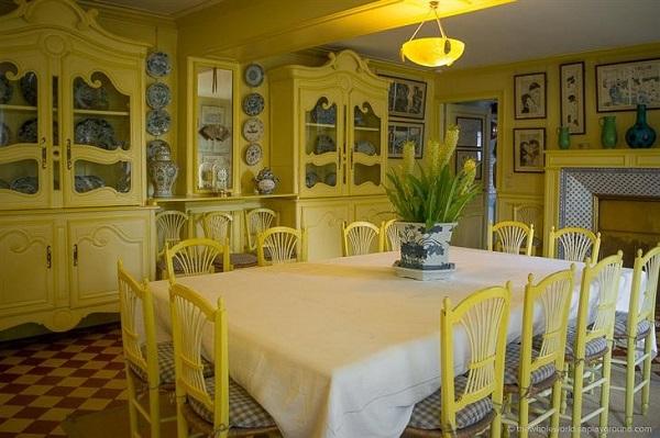 Un comedor de color amarillo brillante con los pisos y trasteros originales.