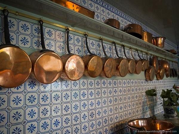 Las cacerolas de cobre están colgadas a lo largo de las paredes de la cocina, sobre azulejos pintados a mano.