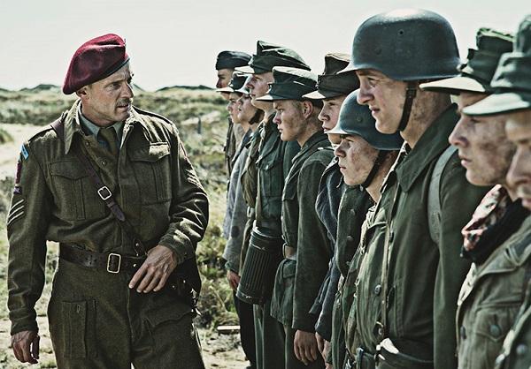 Roland Møller, en su papel del sargento Carl Rasmussen, instruye a su escuadrón de jóvenes alemanes sobre sus deberes, y les hace una promesa: cuando terminen, podrán irse a su casa.