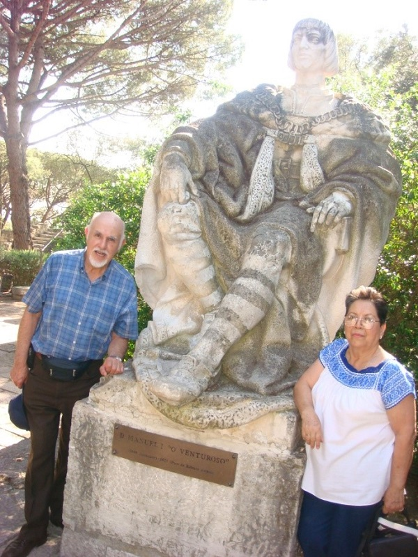 """Manolo y Silvia en el Castillo de San Jorge y ante la estatua de Manuel """"El Venturoso""""."""