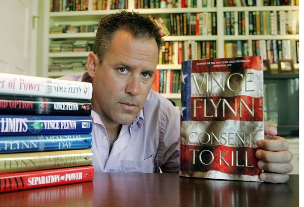 "Best-selling author Vince Flynn poses with the dust jacket of his new book, ""Consent to Kill,"" and copies of his six other books in his home in Edina, Minn., Sept. 2, 2005. Flynn, 39, self-published his first political thriller, ""Term Limits,"" in 1997 before landing a book deal. He credits his sales experience with Kraft General Foods with helping him learn how to promote his first  book at bookstores. (AP Photo/Jim Mone)"