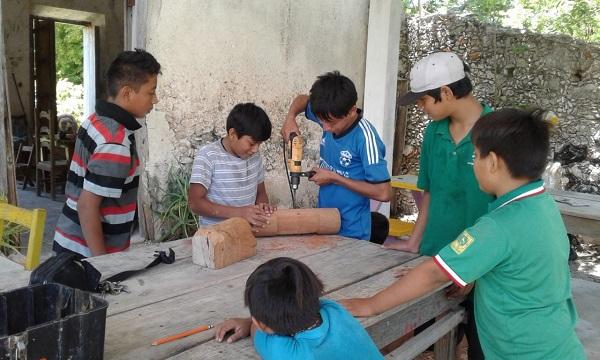 Gaspar muestra cómo se perfora la madera para elaborar un Tun Kul.