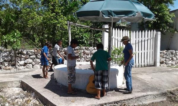 La maestra de CDA con Carlos, Armando, Gabriel y Aarón pintan el pozo.